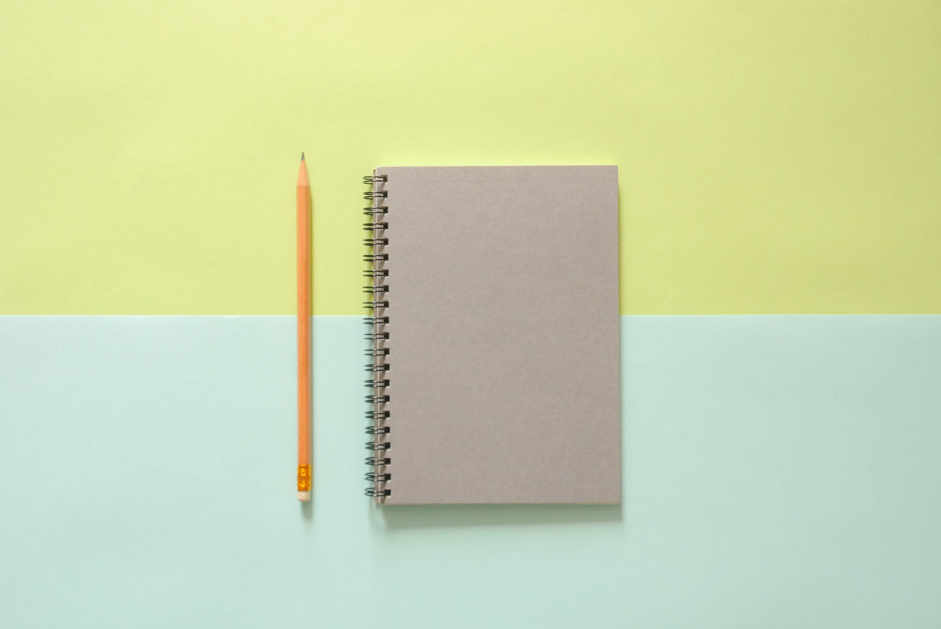 white spiral notebook beside orange pencil