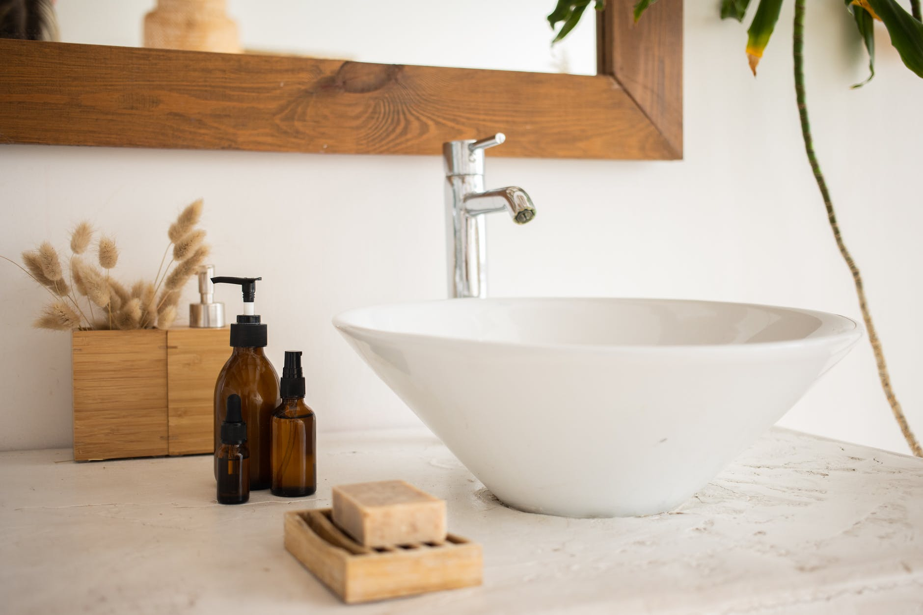 sink with mirror bottles of soap and cosmetic oil in bathroom